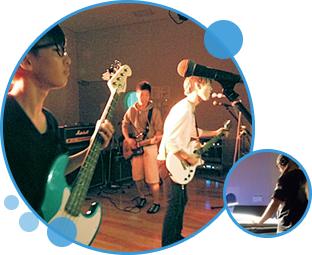 写真:楽器演奏のパフォーマンスをする若者と音響ミキサーを操作する若者。